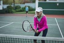 Mujer senior feliz jugando al tenis en la cancha de tenis - foto de stock