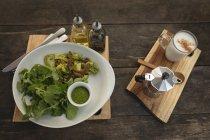 Salat und Kaffee serviert auf einem Holzbrett in einem Coffee-shop — Stockfoto