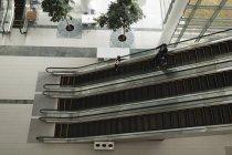 Деловых людей спуститься на эскалаторе в офисе — стоковое фото