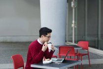 Young man having coffee and breakfast at outdoor cafe — Stock Photo