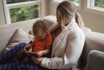 Mutter und Baby sitzen auf dem Sofa und nutzen zu Hause das digitale Tablet — Stockfoto