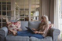 Старші жінки, використання ноутбука на дивані в домашніх умовах — стокове фото