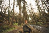 Молодая туристка, сидящая у берега реки в лесу — стоковое фото