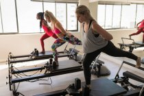 Group of women exercising on stretching machine in fitness studio — Stock Photo