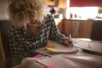 Молода жінка, писати в Блокноті вдома — стокове фото