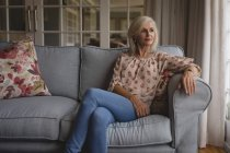 Thoughtful senior woman sitting on sofa at home — Stock Photo
