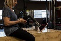 Personnes handicapées mature femme à l'aide de téléphone portable dans la salle de gym — Photo de stock