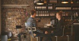 Jeune couple buvant café assis au bar comptoir — Photo de stock