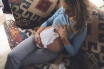 Беременная женщина в детской одежде в гостиной дома — стоковое фото