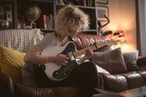 Junge Frau spielt zu Hause im Wohnzimmer Gitarre — Stockfoto