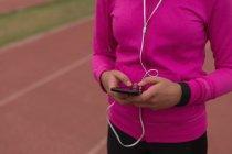 Sezione centrale dell'atleta femminile che ascolta musica sul cellulare — Foto stock