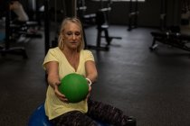 Disabled woman exercising with ball in the gym — Stock Photo