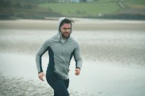 Fit man man in hoodie jogging on beach — Stock Photo