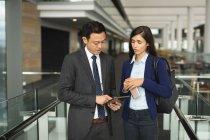 Uomo d'affari e donna d'affari discutono su un tablet digitale in ufficio — Foto stock