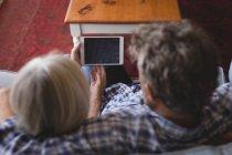 Pareja mayor usando tableta digital en el sofá en casa - foto de stock