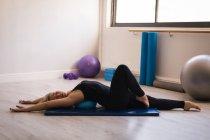 Femme effectuant exercice d'étirement dans le studio de remise en forme — Photo de stock