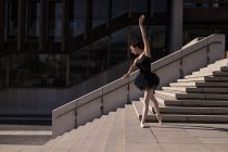 Woman performing ballet on the steps in the city — Stock Photo