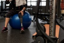 Worried disabled woman sitting on exercise ball in the gym — Stock Photo