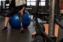 Беспокойная женщина-инвалид, сидящая на мяче в спортзале — стоковое фото