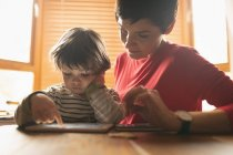 Close-up of mother teaching to son on digital tablet at home — Stock Photo