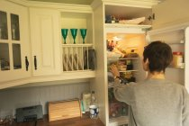 Rear view of woman looking into fridge for food at home — Stock Photo