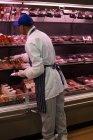М'ясника, вибравши м'ясо з дисплеєм на м'ясний магазин — стокове фото