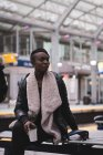 Jovem mulher tomando café na estação ferroviária — Fotografia de Stock
