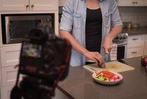 Женщина готовит салат на кухне дома — стоковое фото