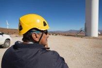 Инженер, стоящий возле ветряной мельницы на ветряной электростанции — стоковое фото
