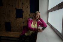 Behinderte ältere Frau benutzt Handy im Fitnessstudio — Stockfoto