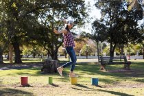 Woman balancing on the colorful stumps in the park on a sunny day — Stock Photo