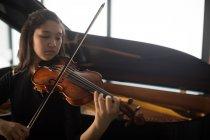 Adorable schoolgirl playing violin in music school — Stock Photo