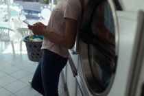 Mid section of woman using her phone while waiting at laundromat — Stock Photo