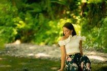 Hermosa mujer sentada en el bosque verde - foto de stock