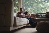 Отец и дочь используют цифровой планшет в гостиной на дому — стоковое фото