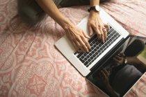 Vista aérea da mulher usando o laptop na cama no quarto em casa — Fotografia de Stock