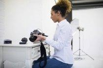 Female photographer removing reel from digital camera in photo studio — Stock Photo
