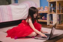 Girl using laptop in bedroom at home — Stock Photo