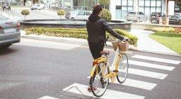 Vista posteriore della donna con attraversamento della strada in bicicletta — Foto stock