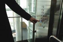 Homme d'affaires appuyant sur un bouton dans l'ascenseur de bureau — Photo de stock