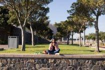Frau ihr Handy überprüfen und mit Smoothie im park — Stockfoto