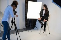 Modelo de mujer posando para una sesión de fotos en estudio fotográfico - foto de stock
