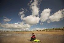 Серфер, сидячи на дошку для серфінгу і, дивлячись на морі на пляжі — стокове фото