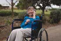 Felice donna anziana sulla sedia a rotelle parlando su un telefono cellulare — Foto stock