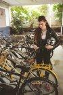 Bella donna che utilizza cellulare al cavalletto della bicicletta — Foto stock