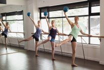 Group of women stretching holding the barre at the gym — Stock Photo
