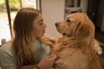 Teenager-Mädchen spielen mit ihrem Hund zu Hause — Stockfoto