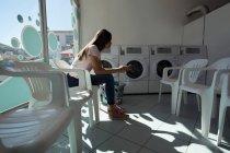 Vue de côté de femme vérifiant son téléphone en attendant à la laverie — Photo de stock
