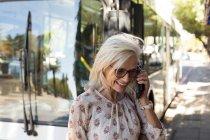 Senior woman talking on mobile phone at bus stop — Stock Photo