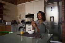 Mujer con teléfono móvil mientras tener el desayuno en casa - foto de stock